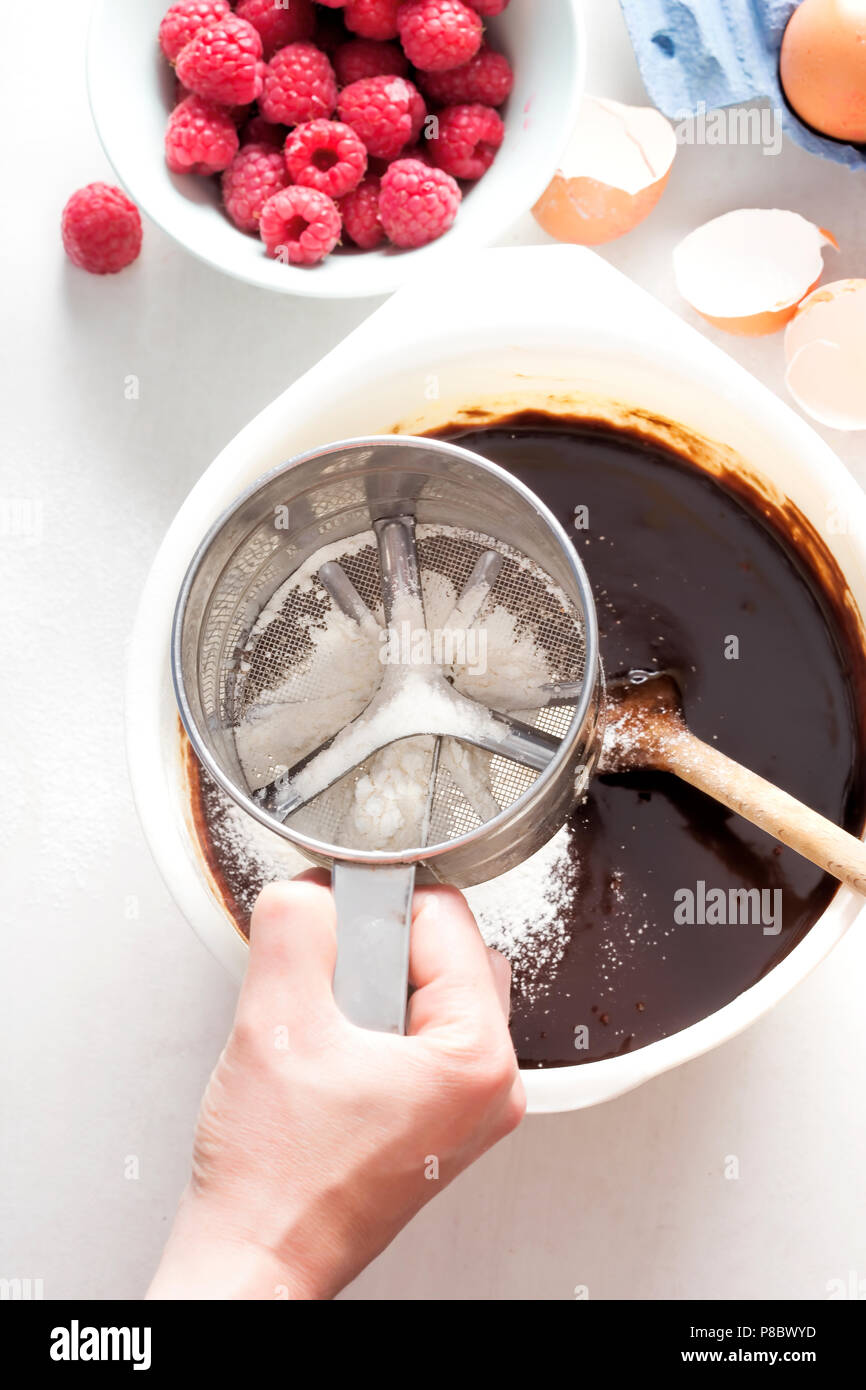 Shifting flour into chocolate brownies batter with wooden spoon, female hands Stock Photo