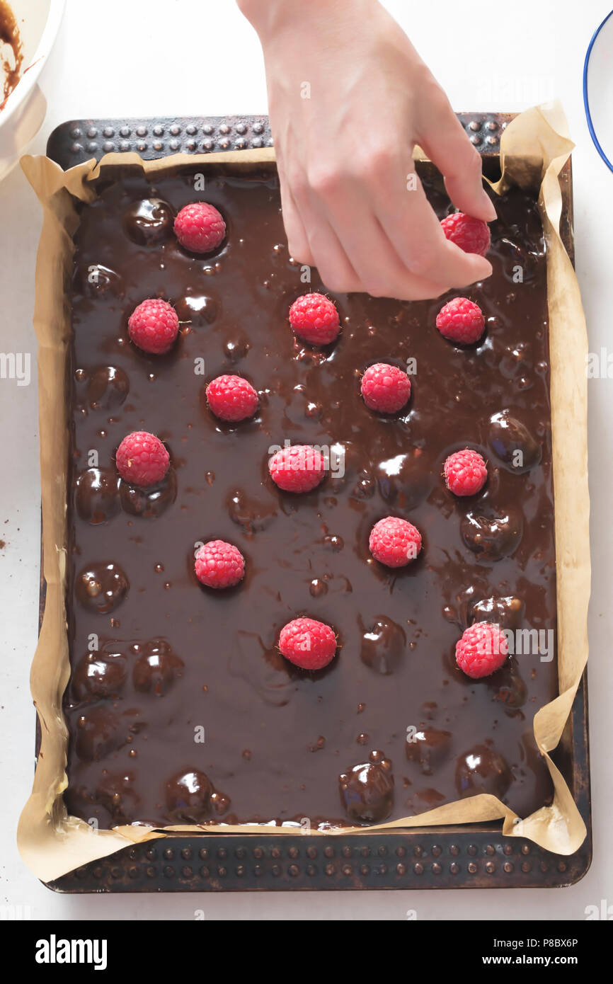 Woman placing raspberries on chocolate brownie batter cake in baking tray with parchment paper - Stock Image