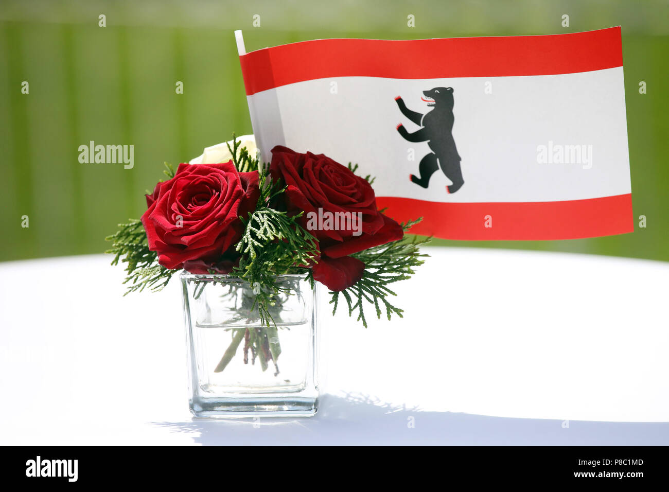 Hoppegarten, Germany, flag of the state of Berlin and red roses in a small vase - Stock Image