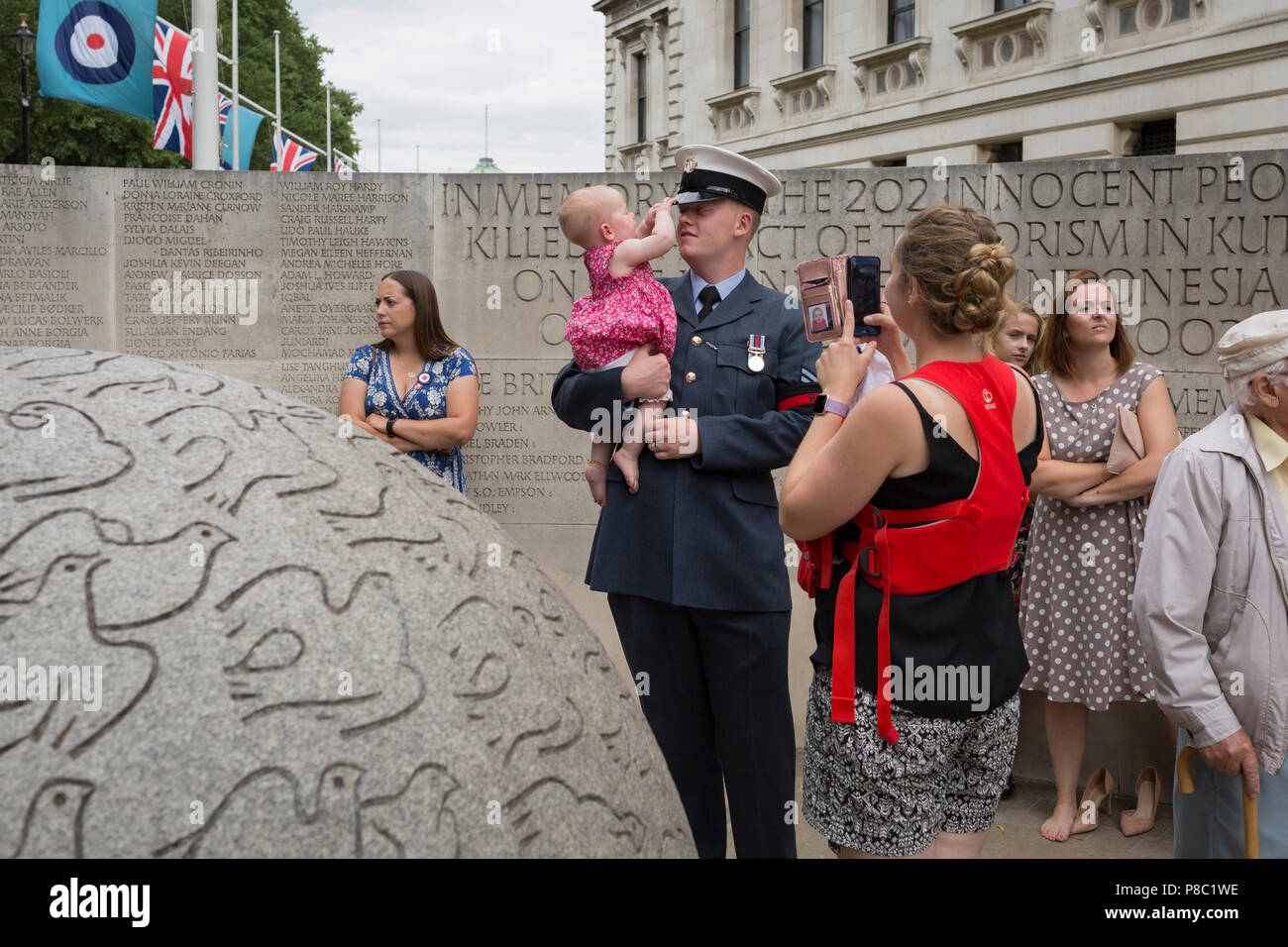 On the 100th anniversary of the Royal Air Force (RAF) and following a flypast of 100 aircraft formations representing Britain's air defence history which flew over central London, a serviceman holds his child next to the memorial to those killed in the 2002 Bali bombing, on 10th July 2018, in London, England. - Stock Image