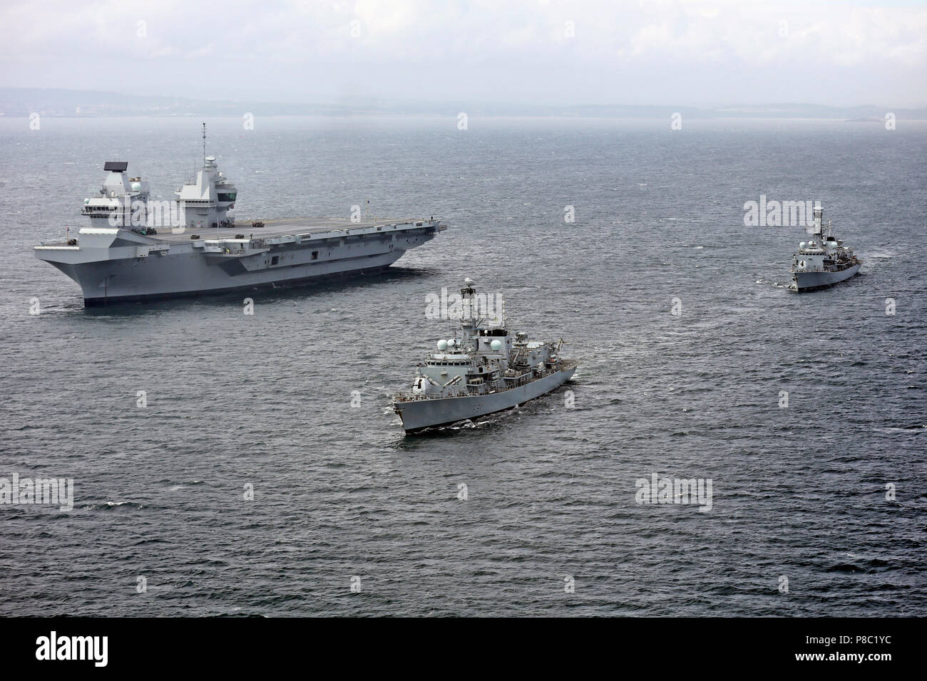 HMS QUEEN ELIZABETH (RO8) aircraft carrier at sea on 28 June 2017 accompanied by  Type 23 frigatesHMS Sutherland (front) and HMS Iron Duke. Courtesy UK Ministry of Defence photo 45162784 - Stock Image