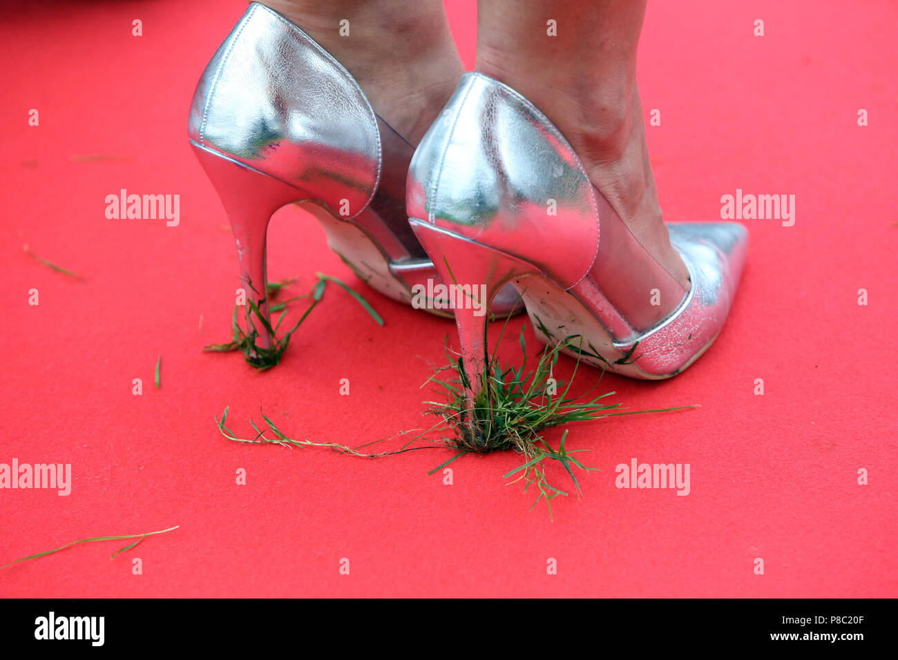Hannover, Germany, grass hangs on the heels of high heels - Stock Image