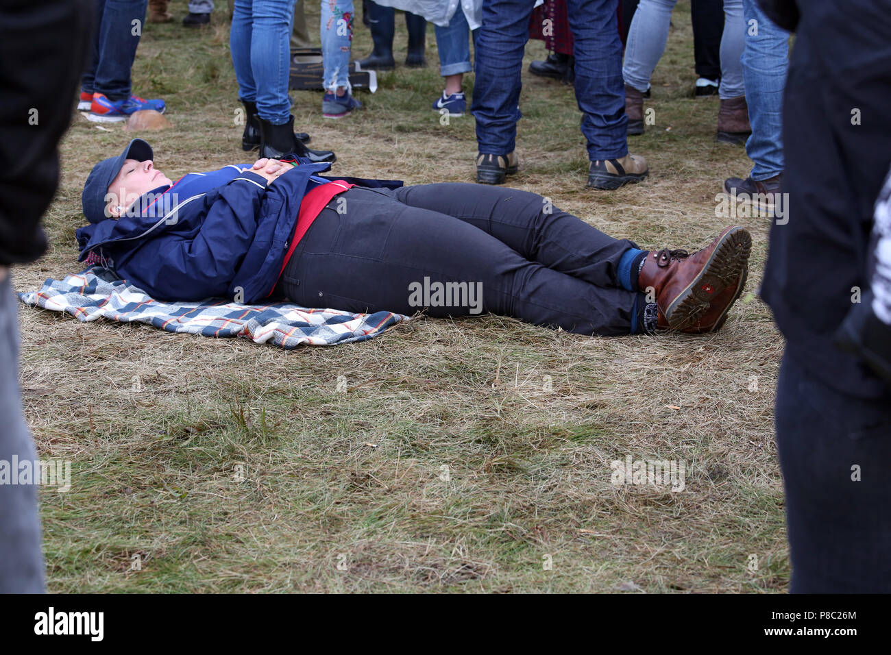 Hoppegarten, Germany, woman is sleeping in the midst of a crowd on the floor - Stock Image