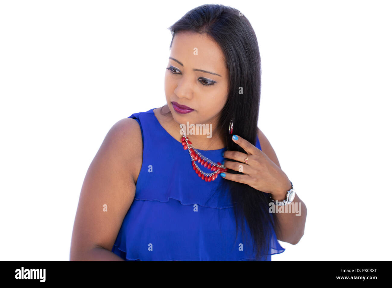 Happy Indian woman, holding hair on white background, hair care concept - Stock Image