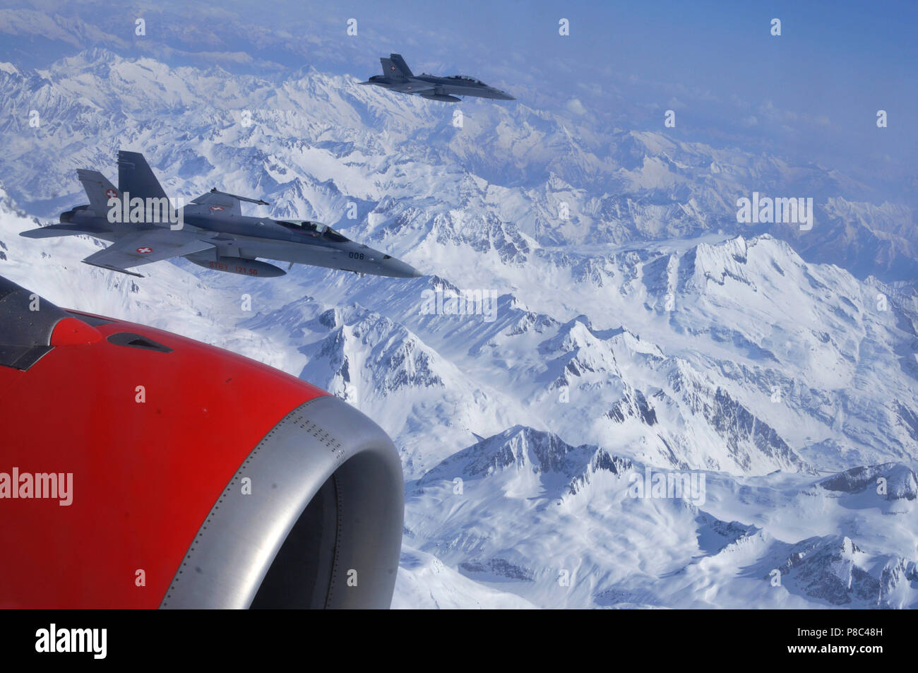 Swiss Alps: Two FA-18 Fighters are esocorting a civil airplaine over the swiss alps covered with snow and ice Stock Photo