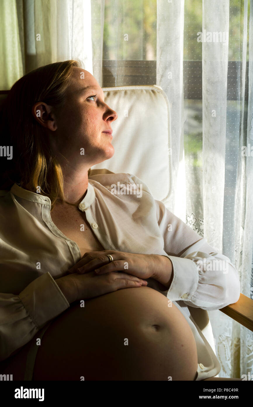 Blonde lady in mid-thirties sitting and caressing her pregnant belly. - Stock Image