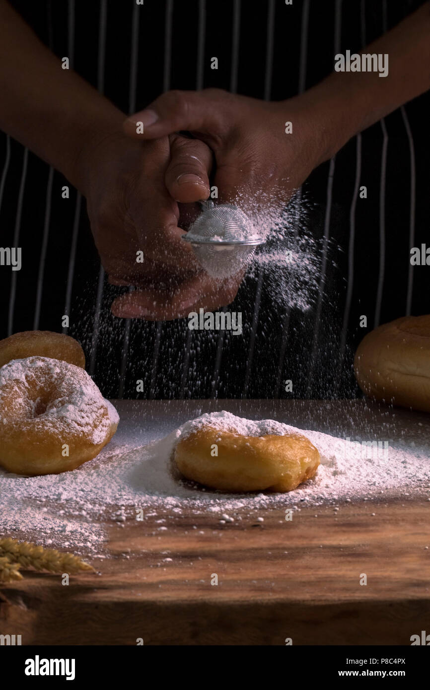 Chef 's hands sprinkling sweet donuts with icing sugar and flour sifter on background.Copy space. - Stock Image