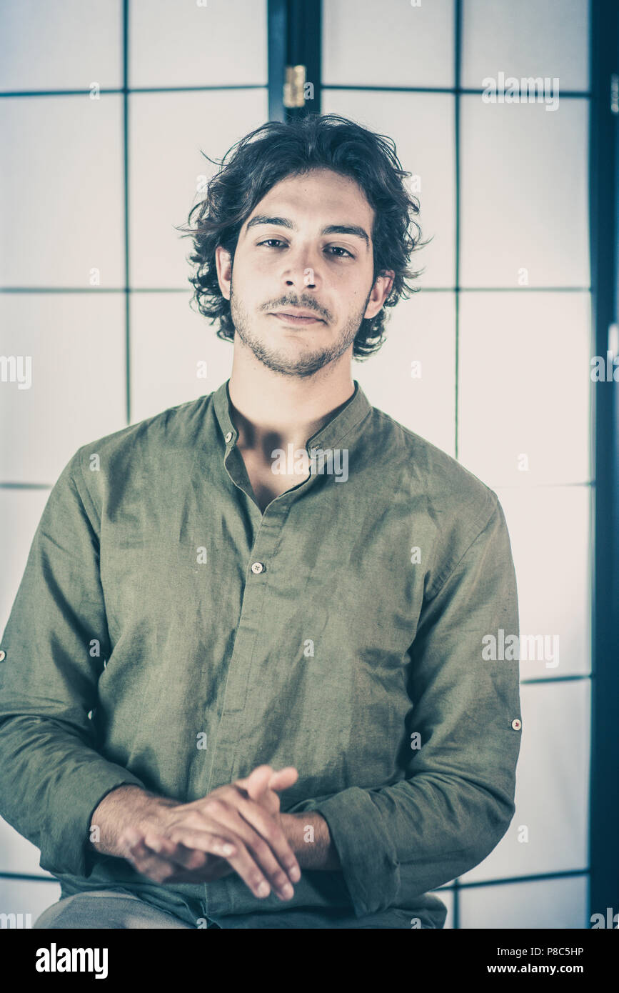 Portrait of Young Man With Raised Hands at Chest - Stock Image