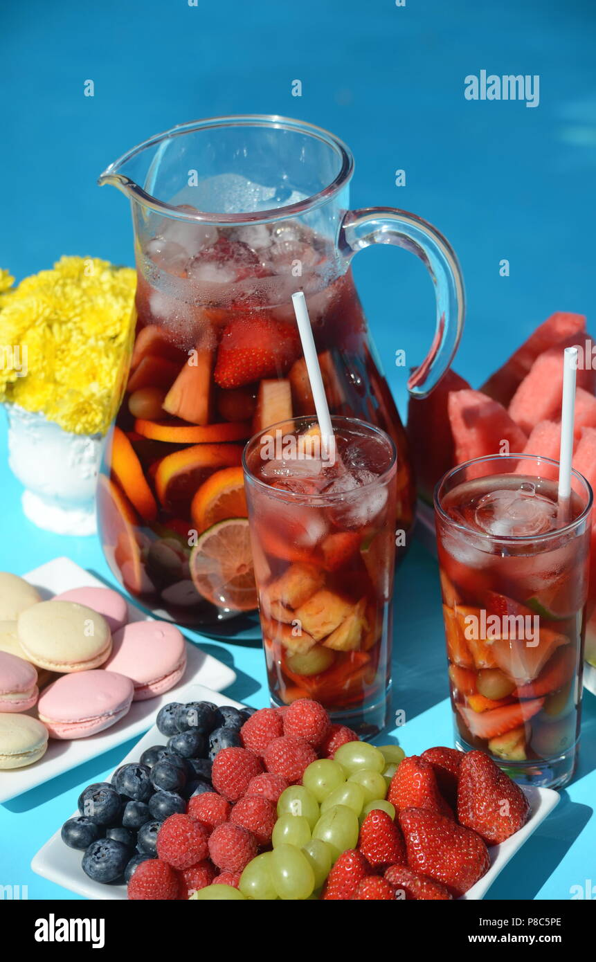 Pool party with sangria pitcher, fruit cocktails and refreshments by the swimming pool. Summer lifestyle, topical vacation, fun and relaxation theme. - Stock Image