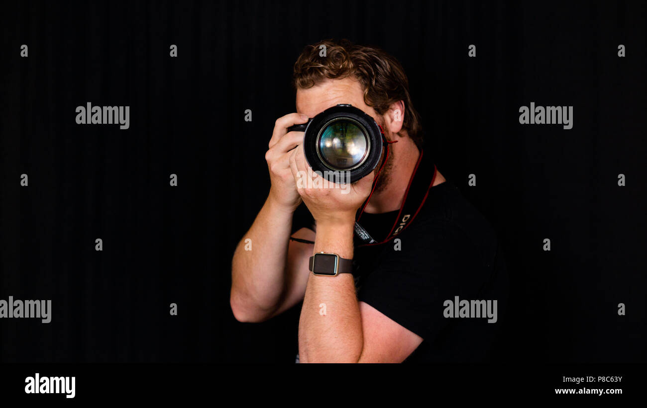 A professional photographer holds his camera close to his face. - Stock Image