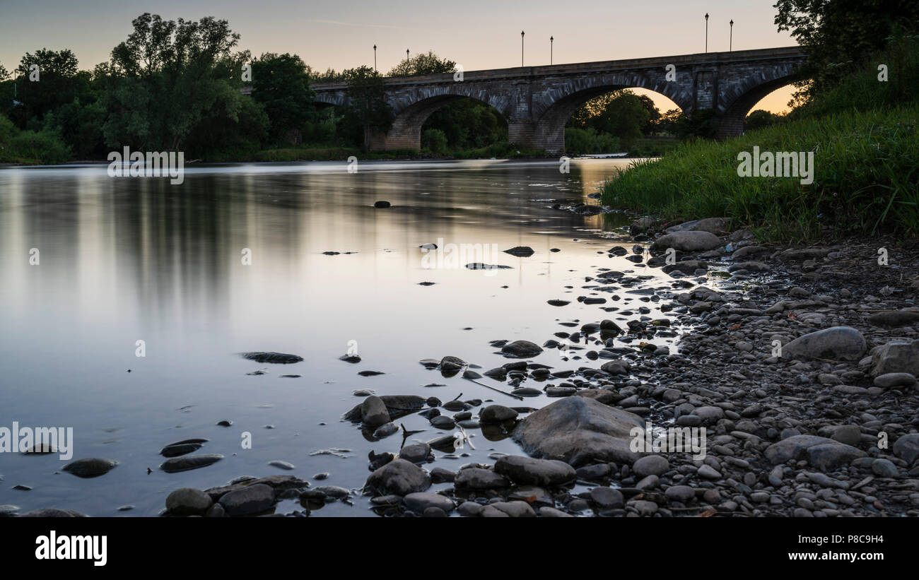 The River Tweed in Kelso Scotland, July 2018 heat wave, low water levels. Summer evening. Rocks normally under water are visible. - Stock Image