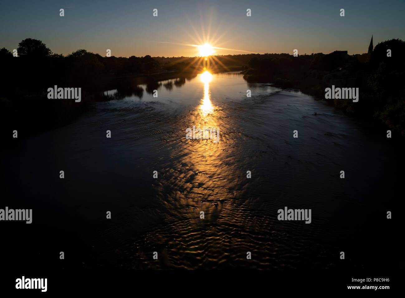 The River Tweed in Kelso Scotland, July 2018 heat wave, low water levels. Summer evening. Sunset, and turbulence in very shallow water over the rocky  - Stock Image