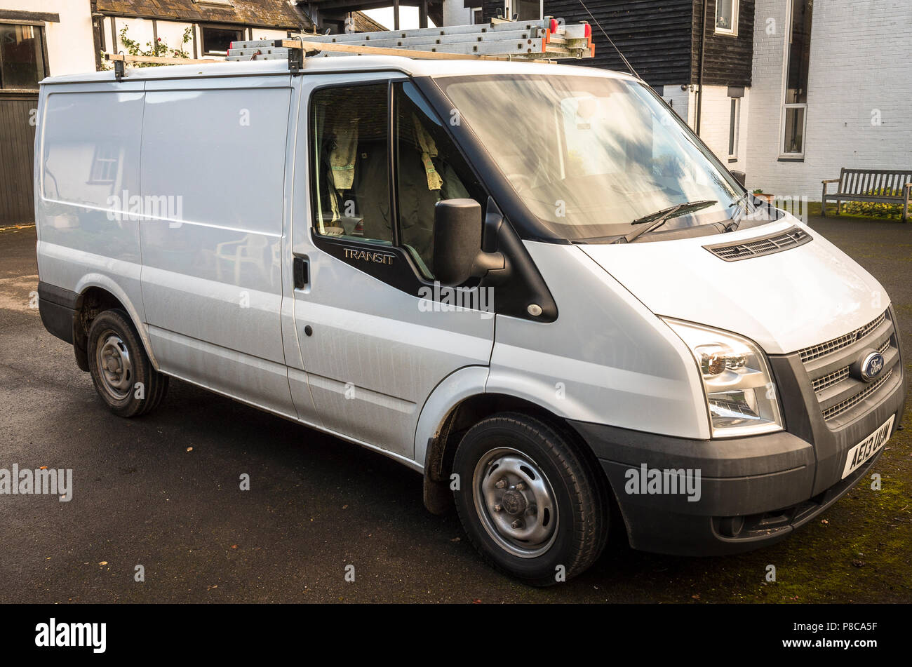Three quarter Side view of white Ford Transit 100 T260 utility business van in UK - Stock Image