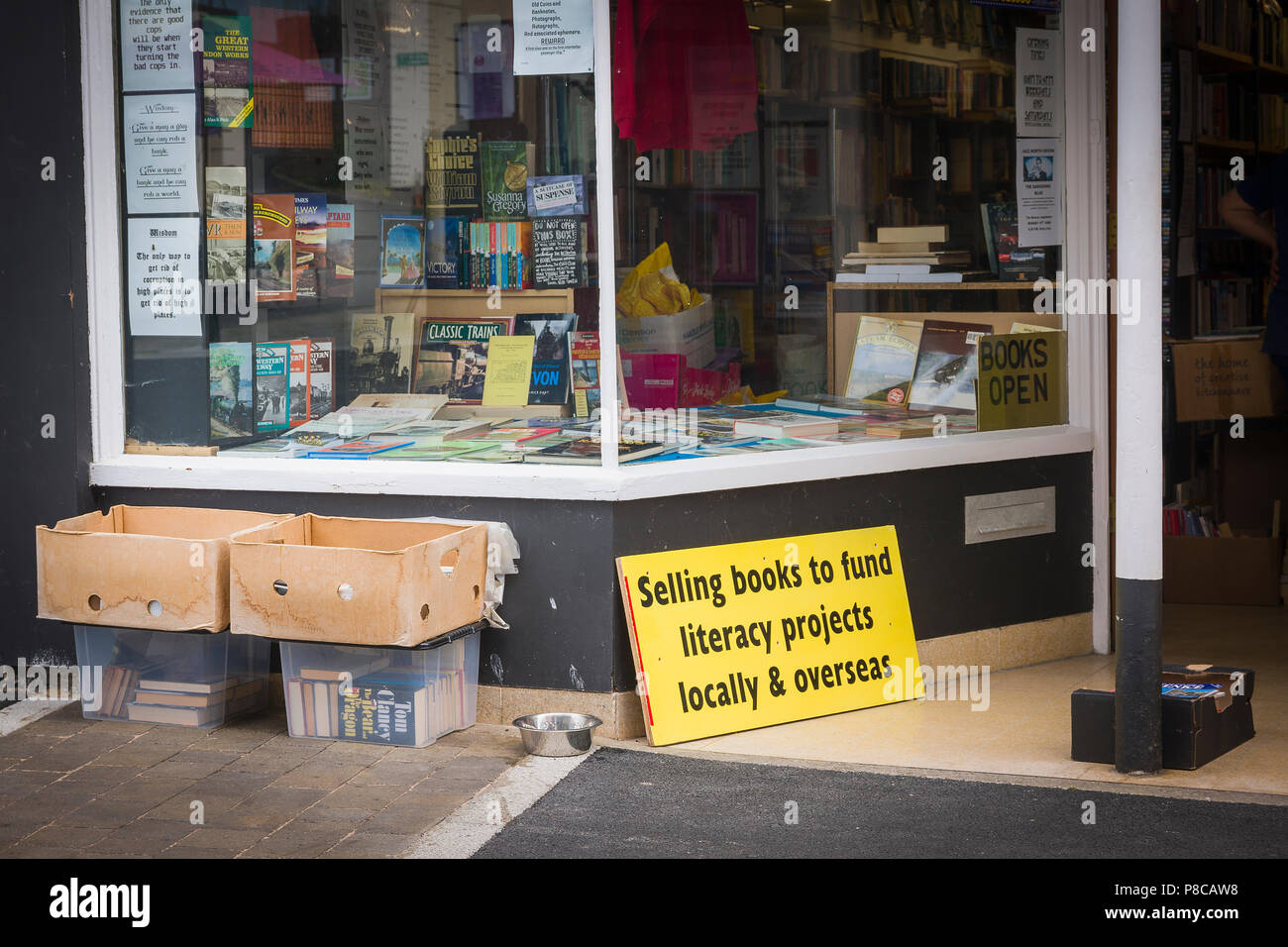 Shop selling old books and remainder stock to fund literacy projects locallyin Devon England  and overseas - Stock Image