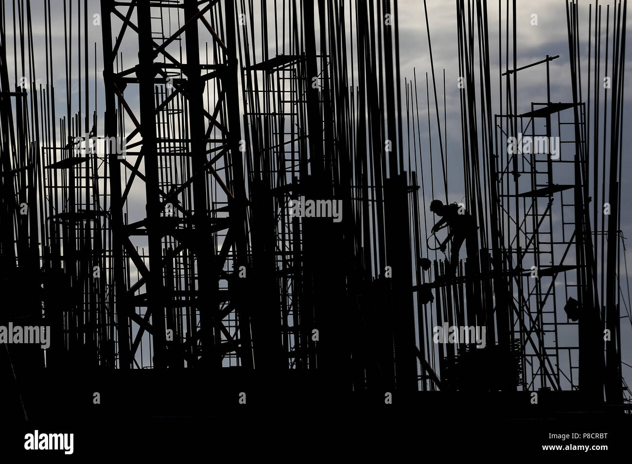 Manila, Philippines. 10th July, 2018. A construction worker stands on top of a scaffolding at a building site in Manila, Philippines on Tuesday. July 10, 2018. Philippines President Rodrigo Duterte is set to have his third State of the Nation Address (SONA) on July 23 where he will highlight his achievements since taking office, such as infastructure and economic development projects. Credit: Basilio H. Sepe/ZUMA Wire/Alamy Live News - Stock Image