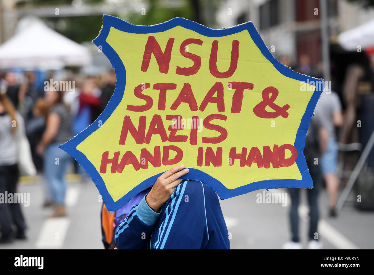 """Germany, Munich. 11th July, 2018. Demonstrators hold a sign saying """"NSU State & Nazis hand in hand"""" at a rally in front of the Higher Regional Court. Today a verdict against Zschaepe will be announced at the National Socialist Underground trial. The so called National Socialist Underground terrorist group has killed 10 people in Germany in the years 2000 to 2007. Credit: Tobias Hase/dpa/Alamy Live News Stock Photo"""