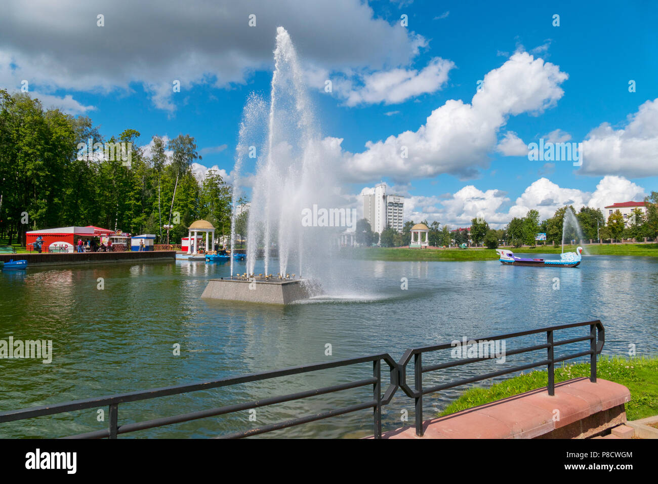 A boat sailing along a lake with a high fountain on a blue sky background. A place for the rest of the city dwellers . For your design - Stock Image