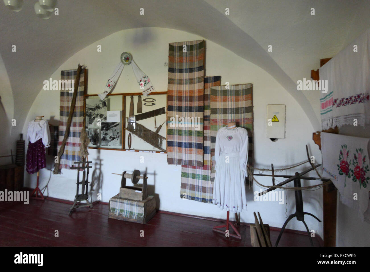 Exposition room seamstresses of old times. On the walls are embroidered towels, sewing tools, as well as traditional embroideries on mannequins . For  - Stock Image