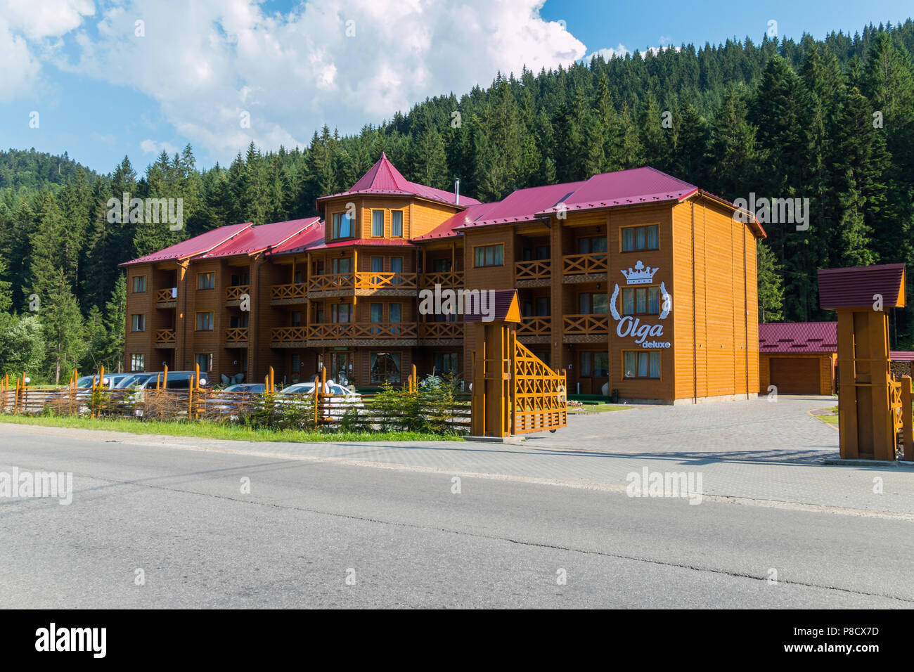 Three-storey hotel complex from a wooden frame on a background of green spruces . For your design - Stock Image