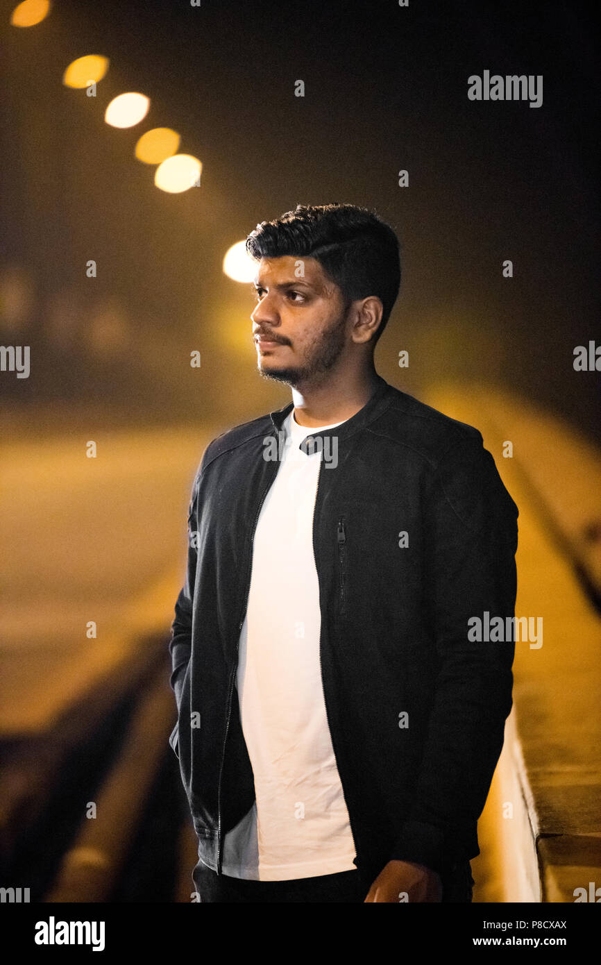 Waist up, outdoor portrait of a young adult Indian boy in black casual jacket over bokeh background. - Stock Image