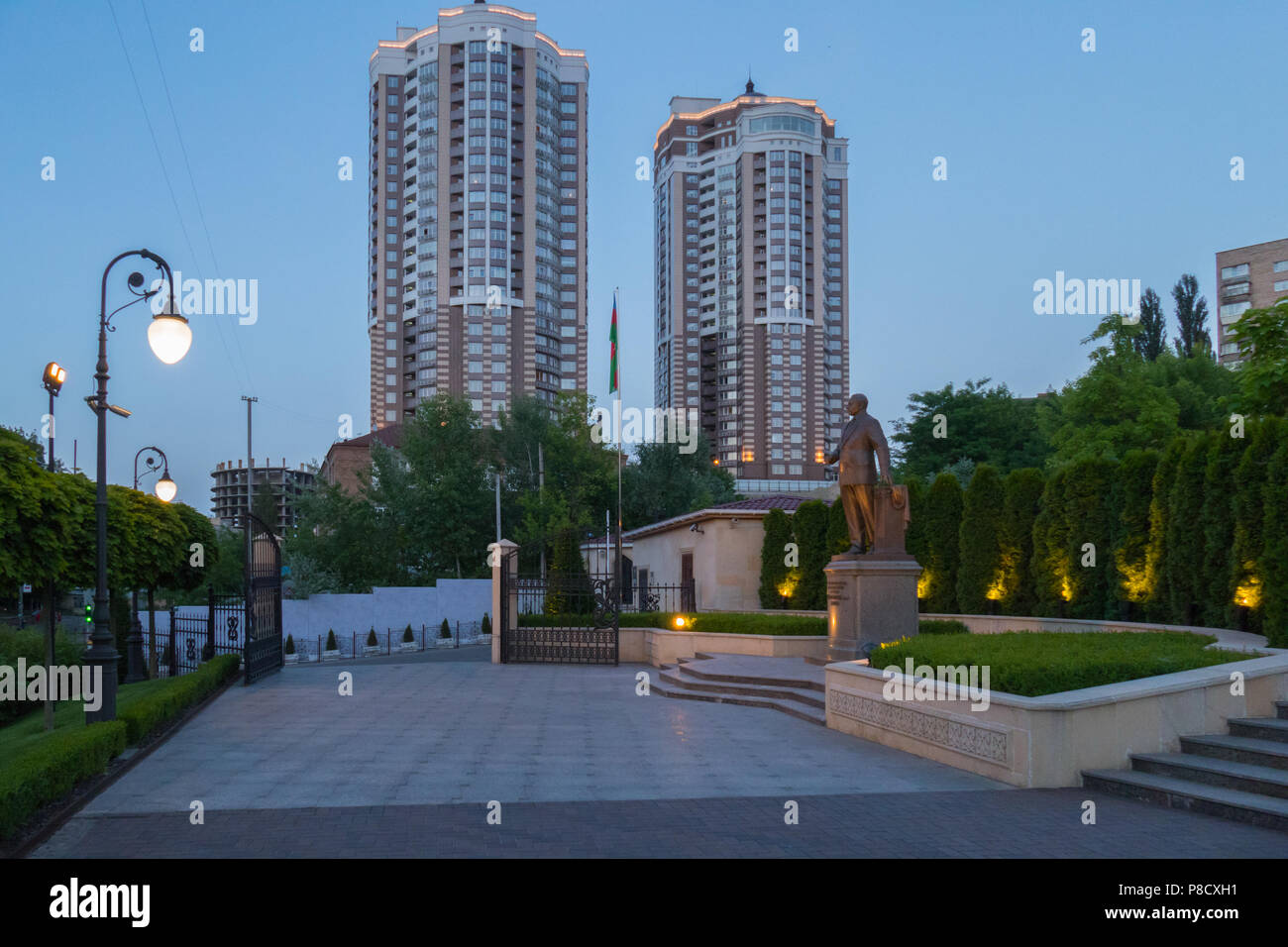 evening landscape of high-rise buildings propping up the firmament and a monument in the green of trees against their background . For your design - Stock Image