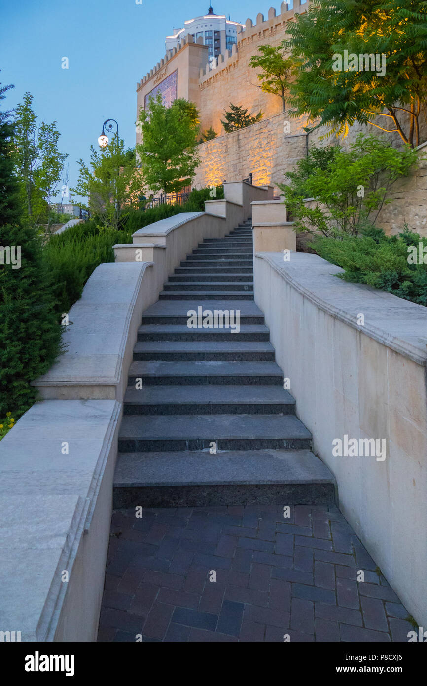 Narrow Staircase With Handrails Going Upwards To A High Wall With An