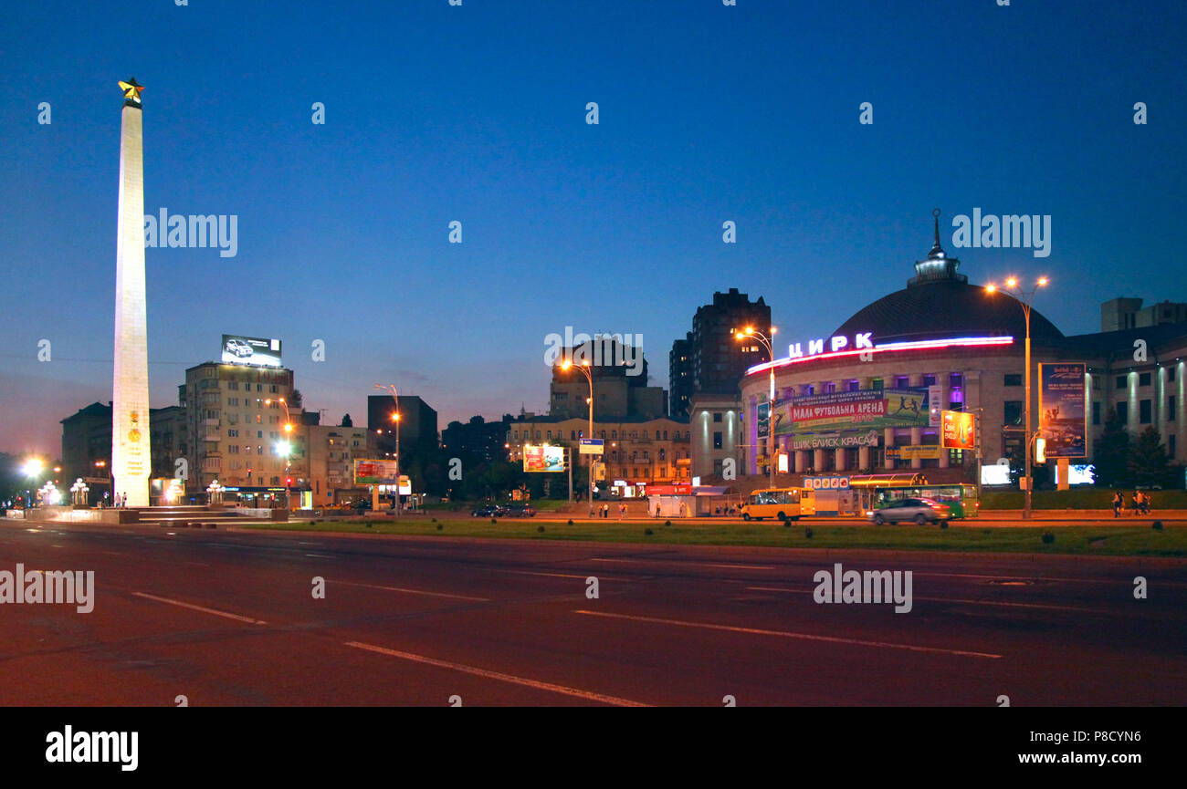 Evening landscape of the lights of the city avenue with bright glowing nameplates and a high memorable sign in the foreground with a star on top. . Fo - Stock Image