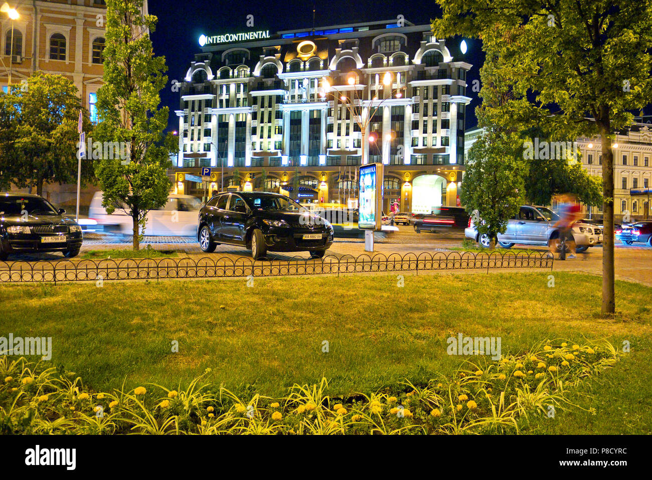 View of the evening city with a beautiful building of a high hotel green lawns and parked on the sidewalks by cars. . For your design - Stock Image