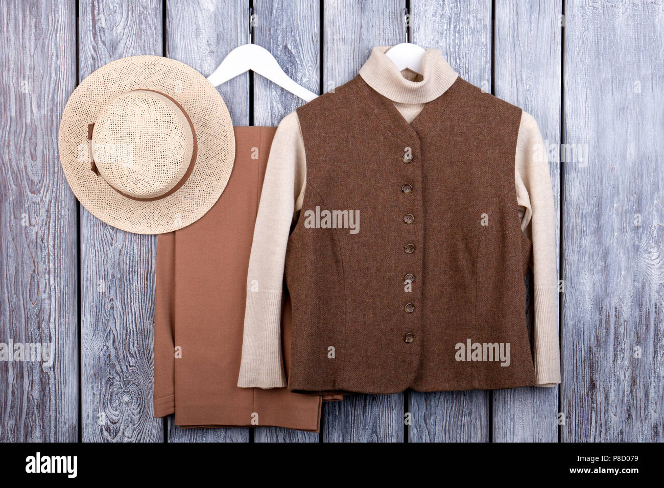 Flat lay, brown vest, trosuers and straw hat. - Stock Image
