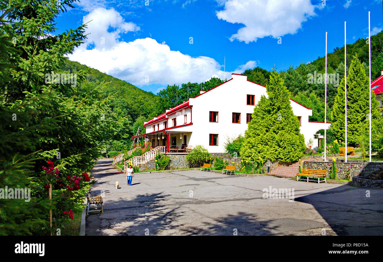 Three-storey country house near a road with benches against a background of spruces . For your design - Stock Image