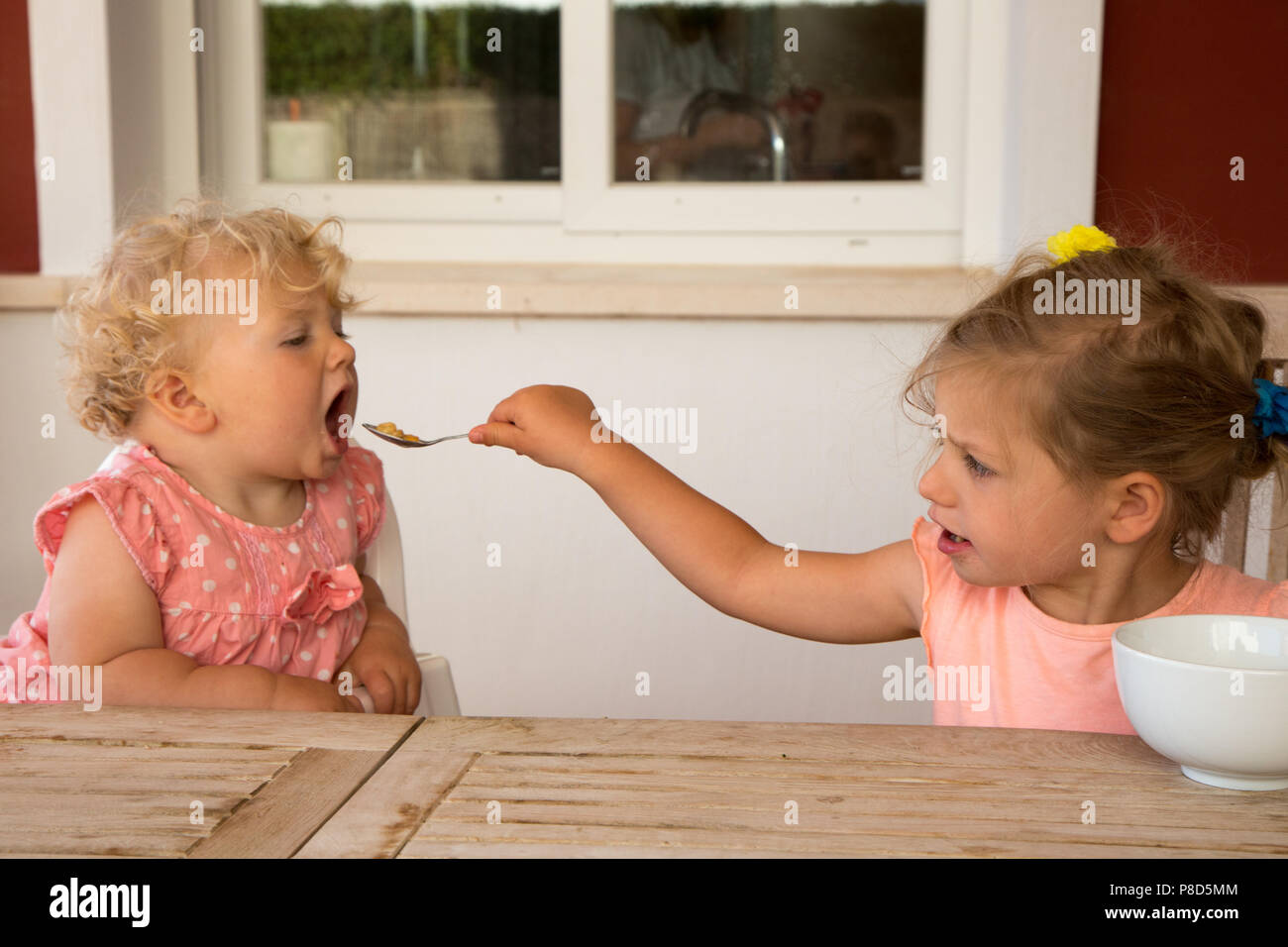 A two year old girl is feeding her younger sister breakfast cereal.The elder girl is 2 and a half and the younger 13 months. - Stock Image
