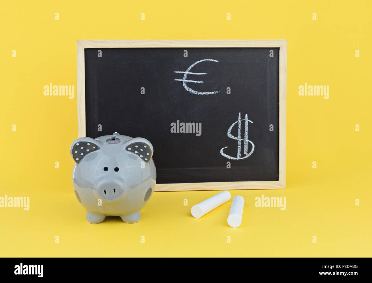 Funny pig piggy bank on background of chalk board with signs of the Euro and Dollar. Concept of studying exchange rate statistics - Stock Image