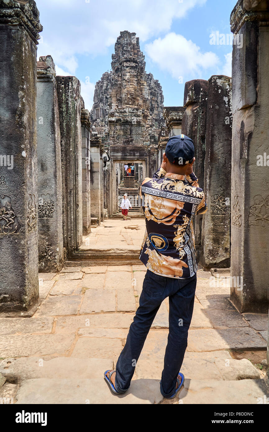 Chinese tourist photographs Face Tower at Angkor Thom - Stock Image