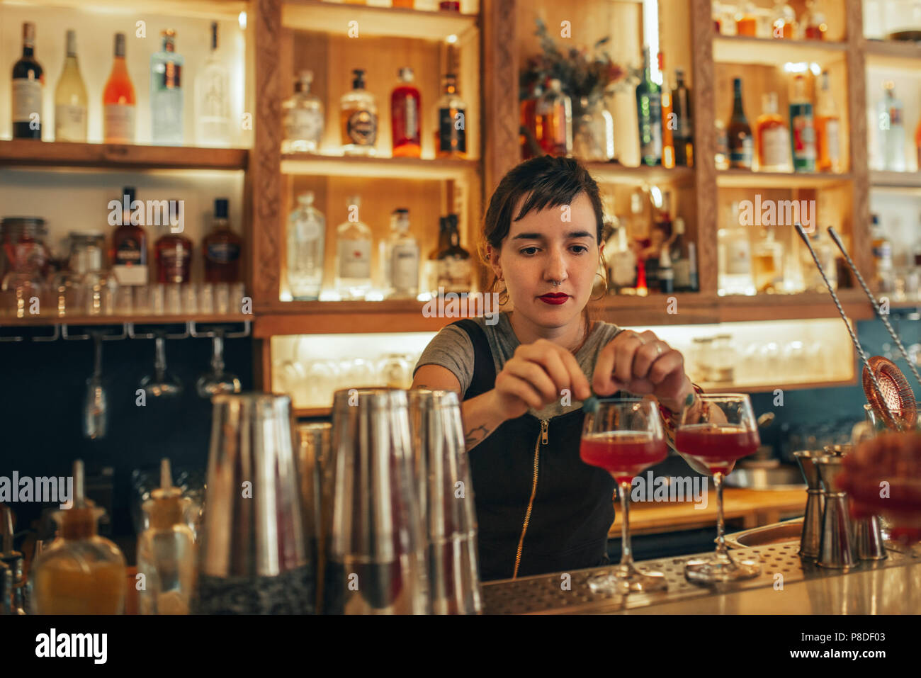 Young female bartender standing behind a bar counter making cocktails  - Stock Image