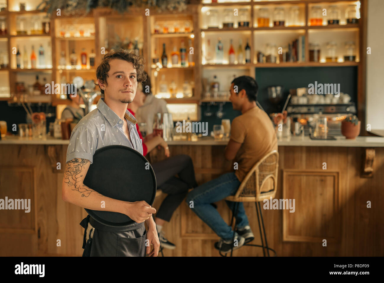 Waiter standing in a trendy bar ready to serve customers - Stock Image