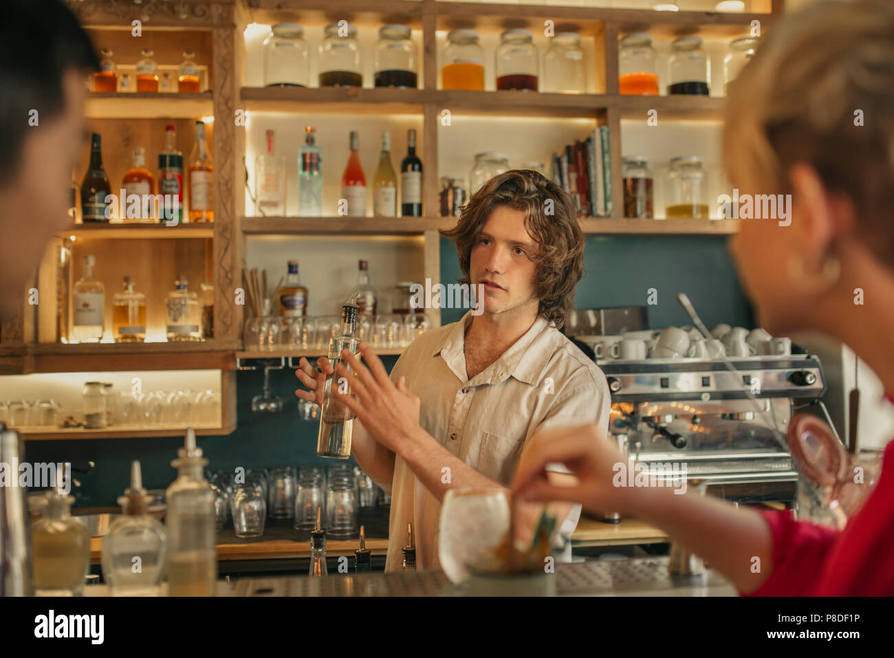 Bartender taking drink orders from customers in a trendy bar - Stock Image