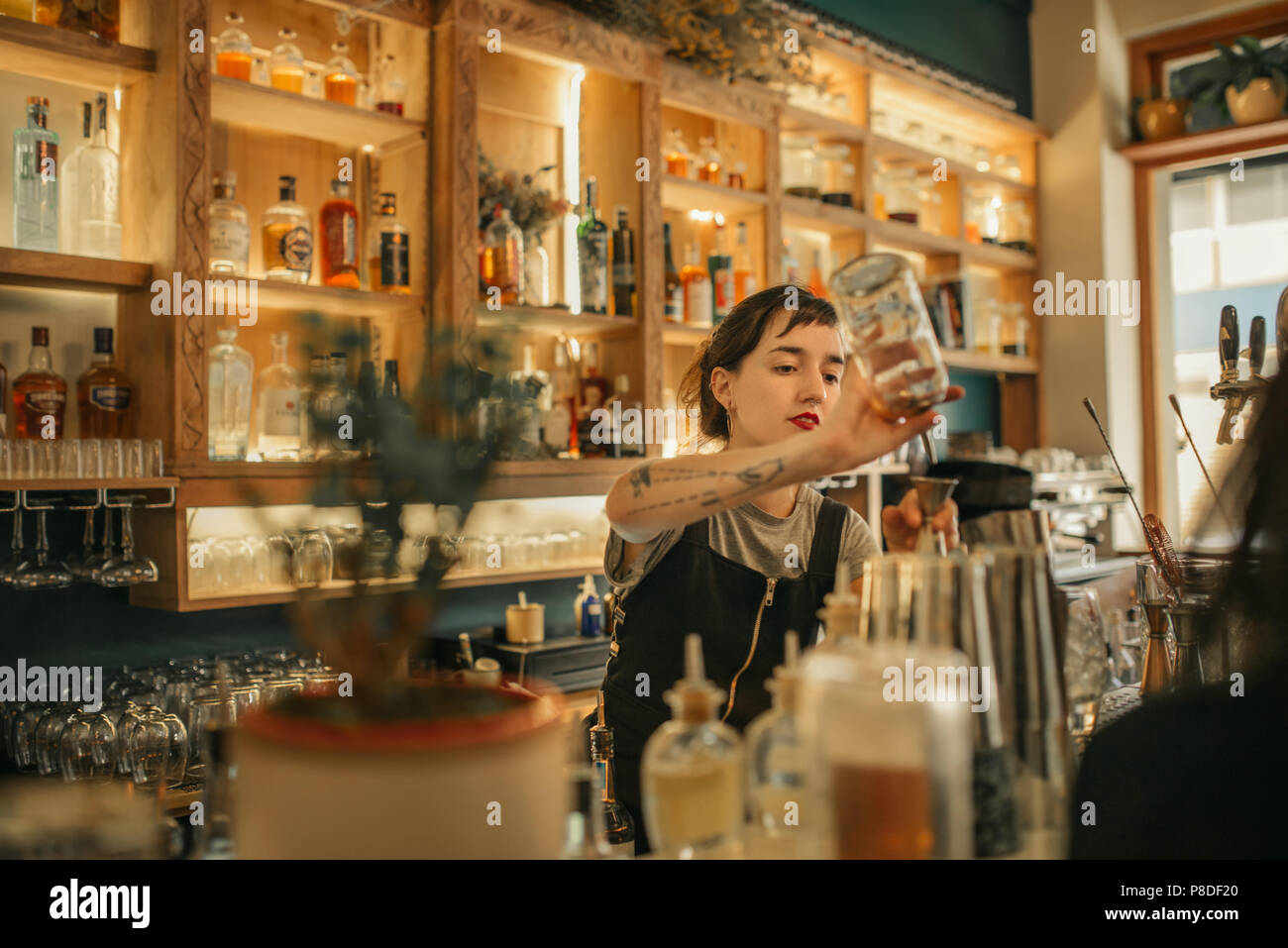 Young female bartender pouring cocktails behind a bar counter - Stock Image