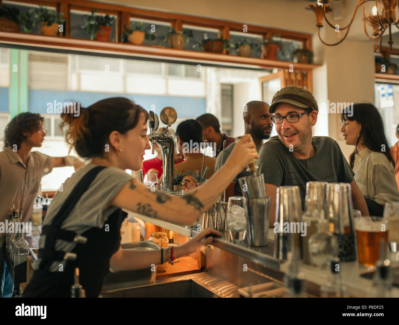 Smiling patron ordering drinks in a trendy bar - Stock Image