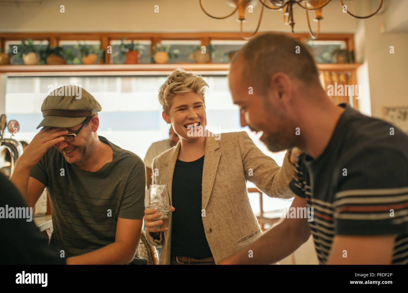 Friends laughing and having drinks together in a bar - Stock Image