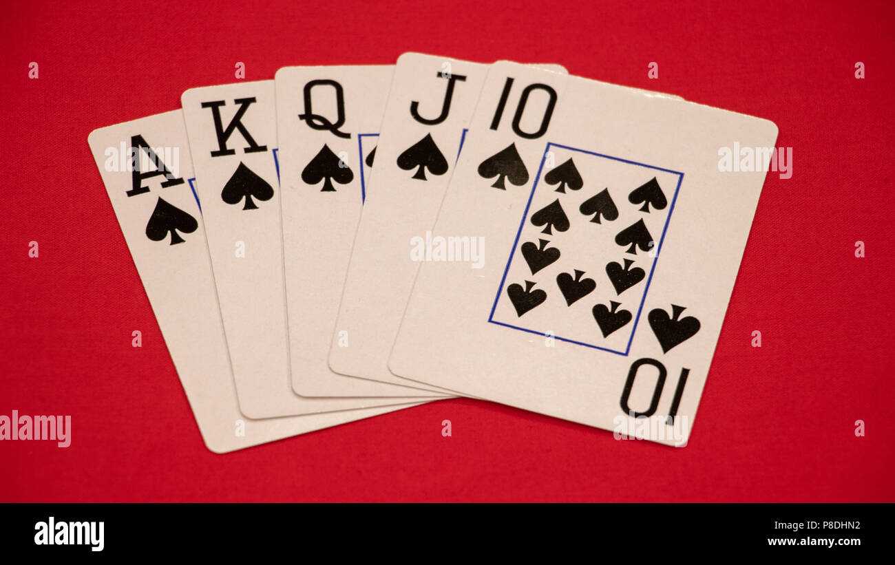 Royal flush poker hand on red background. - Stock Image