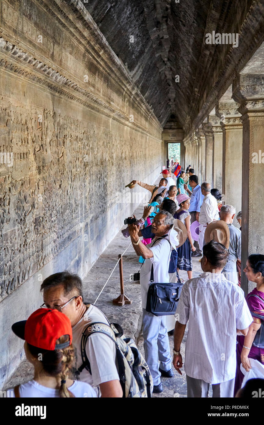 Tourist looking at bas-relief in Angkor Wat, Siem Reap, Cambodia - Stock Image