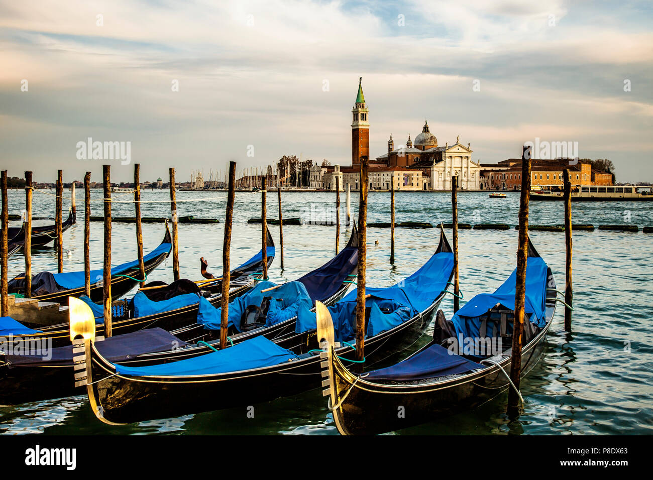 Gondolas docked in Venice, Italy in the morning.  In the background is the island of San Giorgio Maggiore Stock Photo