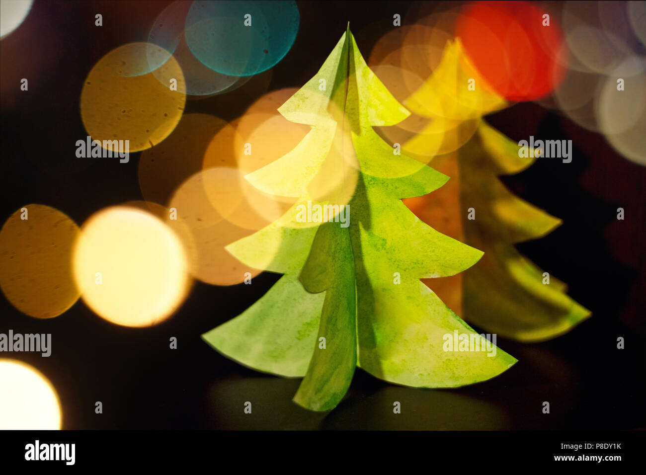 Merry christmas and happy new year greeting card with bokeh effect. New year celebration holiday background.Abstract Blurred Bokeh Holiday Backdrop.design card. Christmas tree paper craft. - Stock Image