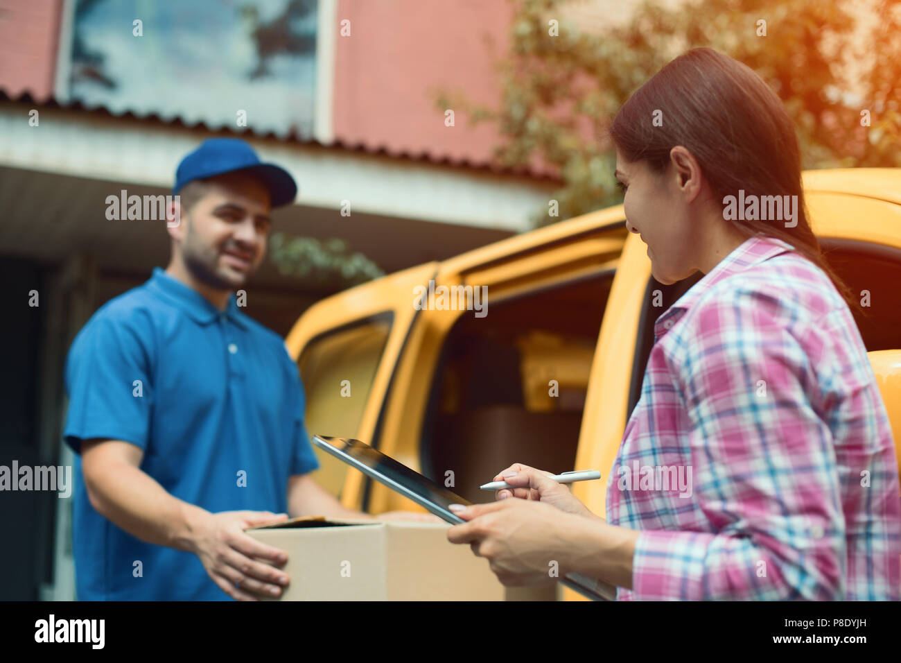 Delivery man handing package box. - Stock Image