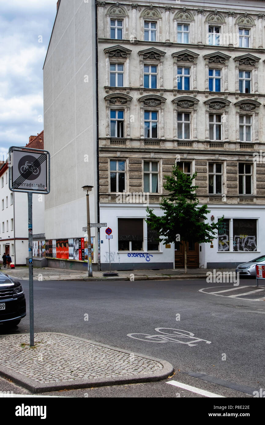 Berlin,Mitte.Street view of old apatment building exterior & facade and cycling street.Bicycle sign gives cyclists preferential use in Choriner str - Stock Image