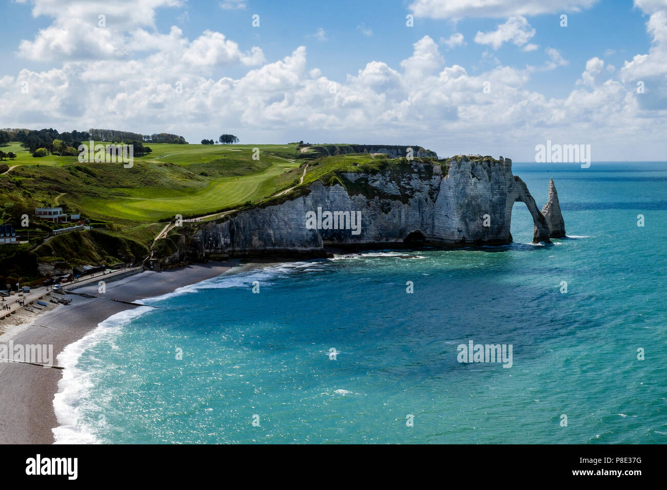 The well manicured greens of Etretat golf course on the cliff top of Etretat bay above L'Aiguille or the Needle sea stack and a natural stone arch. - Stock Image