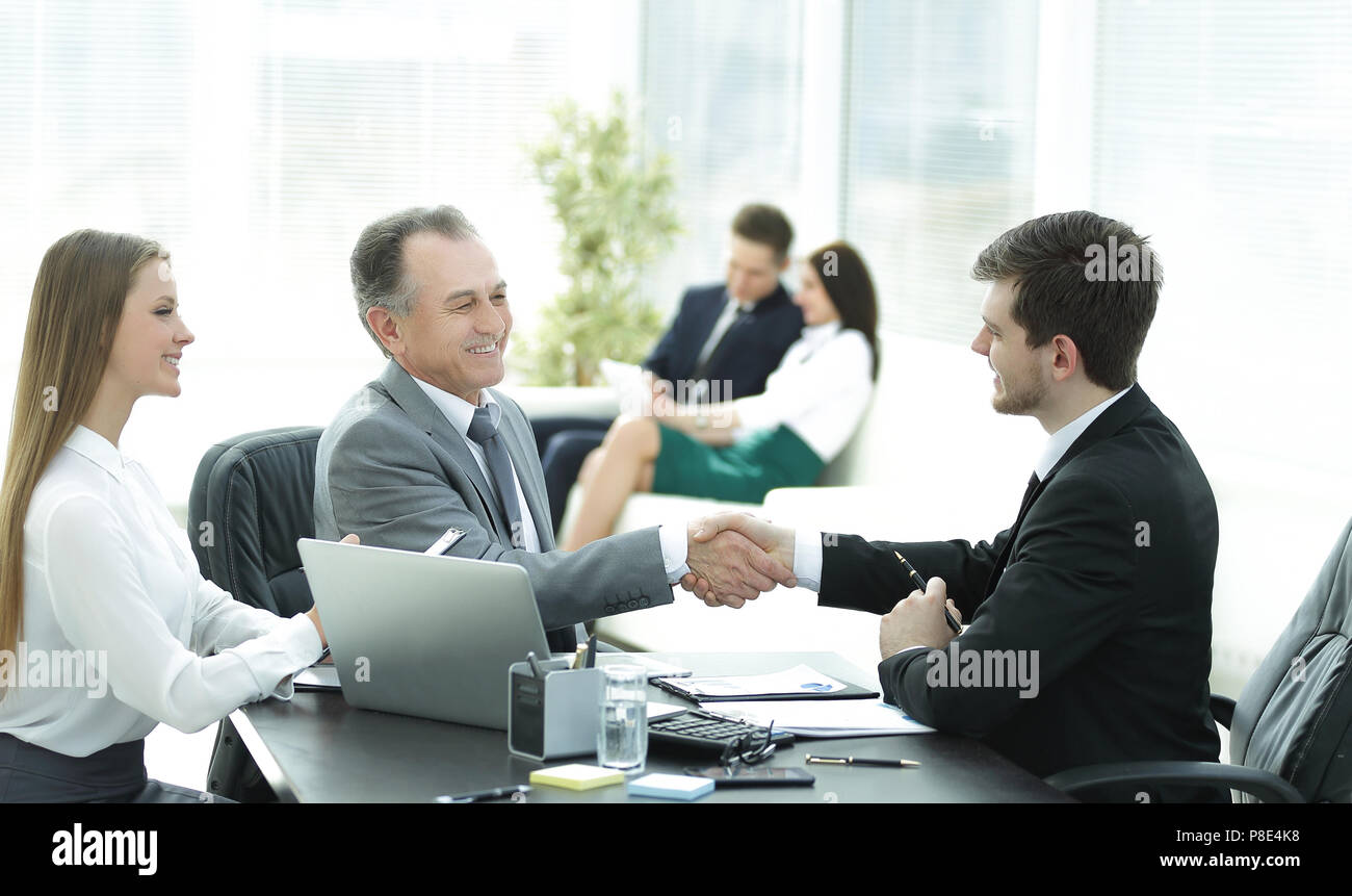 handshake business people behind a Desk in the office - Stock Image