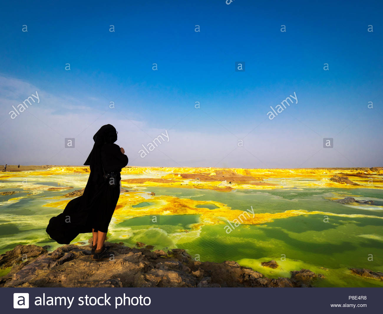 Woman with burka, geothermal area with sulphur deposits and acid salt varnishes, Dallol, Danakil Valley, Ethiopia - Stock Image