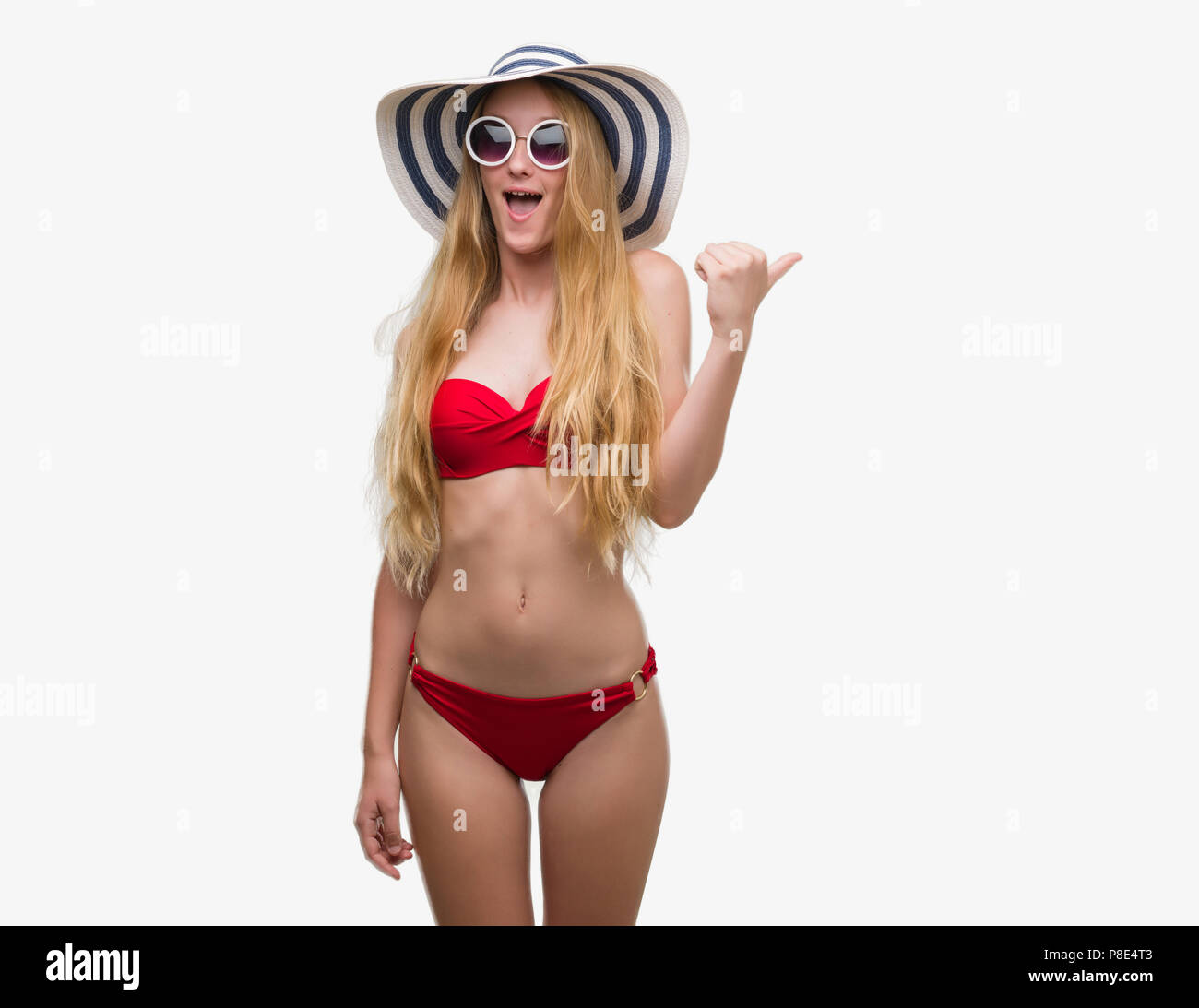 Blonde teenager woman wearing bikini, sunglasses and summer hat pointing and showing with thumb up to the side with happy face smiling Stock Photo