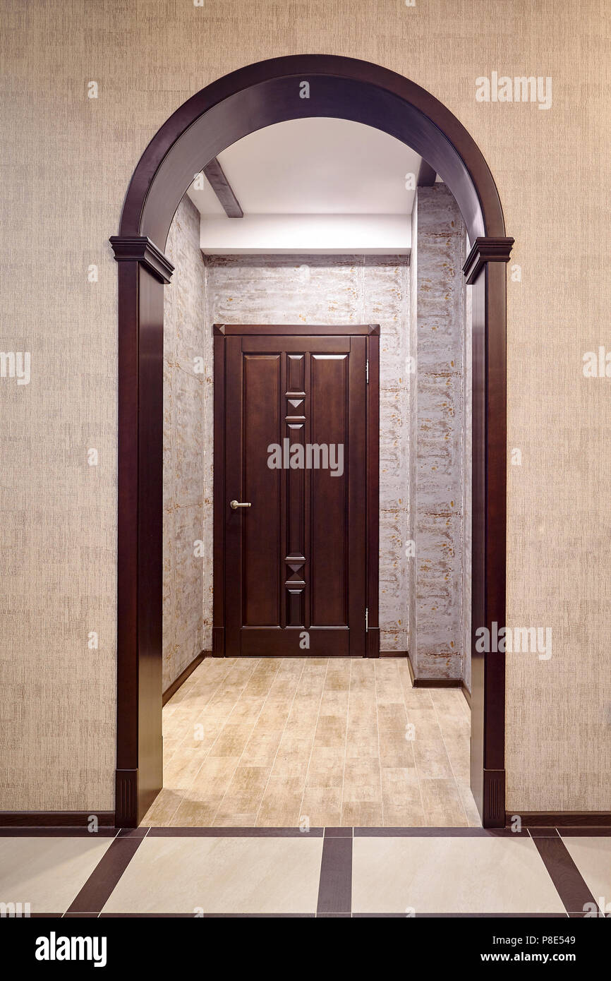 Passage through wooden archway into corridor with entrance door tiked in brown tones example of modern interior of house - Stock Image